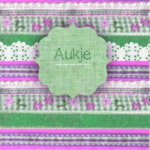 Een handwerk geboortekaartje opgebouwd uit stofjes, breisels, knoopjes en stiksels.