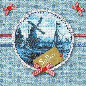 Een geboortekaartje in het thema Holland met geborduurd molentje. Een heel Hollands handwerkje met kant, stiksels en strikjes.